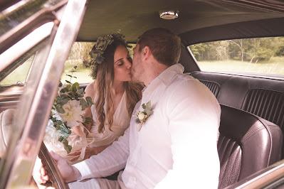 Pareja de novios besándose en el coche nupcial