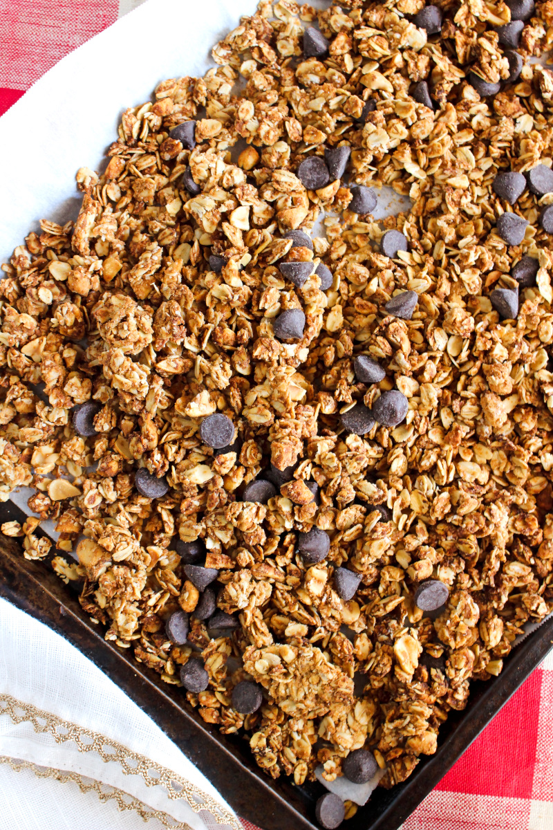 Chocolate Chip Peanut Butter Granola on a parchment-lined baking sheet on a red and white checkered background.