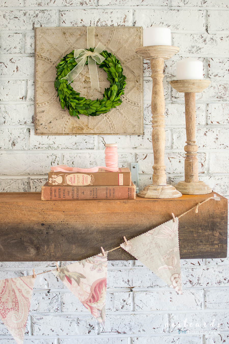 spring mantel with wood candlesticks and fabric banner