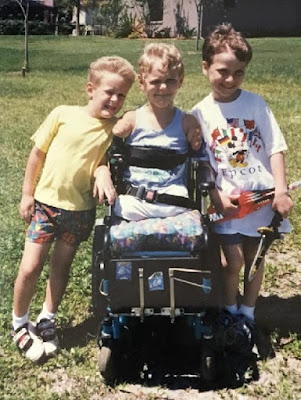 A picture of three boys, standing shoulder-to-shoulder. The middle child is a power wheelchair user