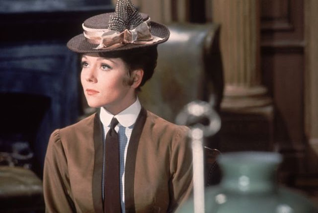 Diana Rigg wearing a hat and brown dress in The Assassination Bureau