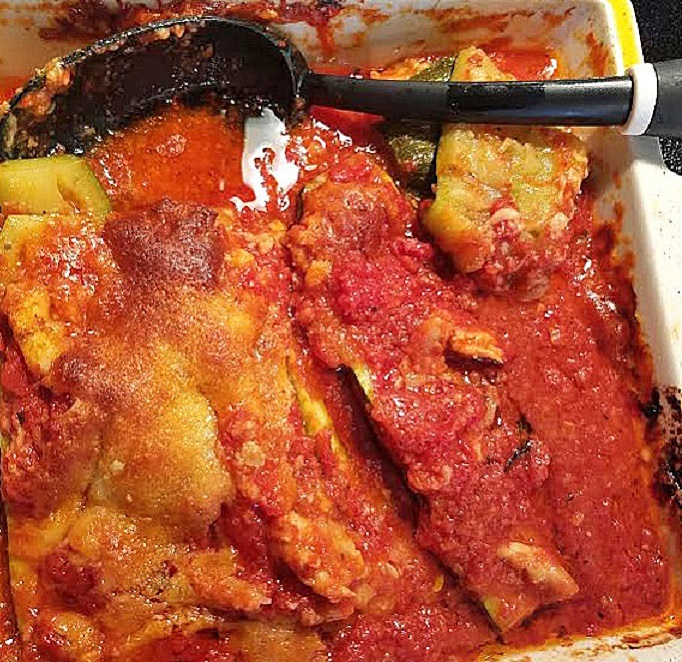 this is chicken stuffed into zucchini with cheese and tomato sauce
