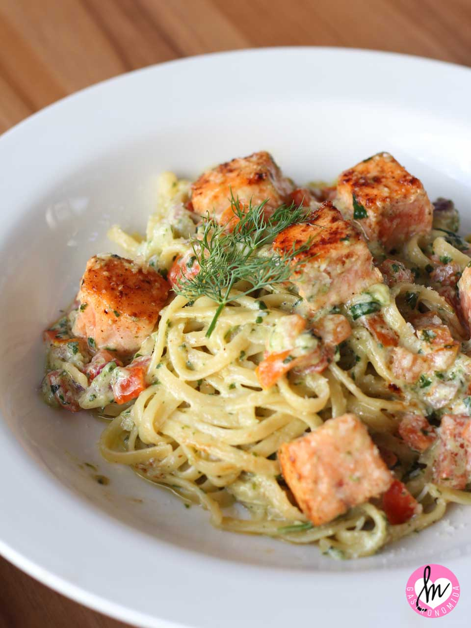 Linguini pasta with tomatoes, parmesan, and pesto cream topped with chunks of salmon