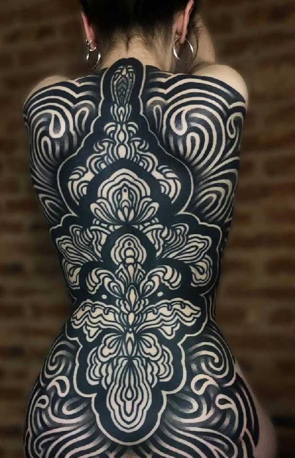 Vemos la espalda de una mujer con tatuajes geométricos en blanco y negro
