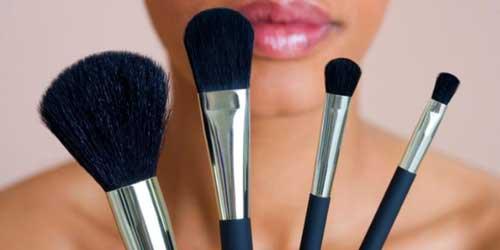 Chica de piel negra con brochas de maquillaje en la mano