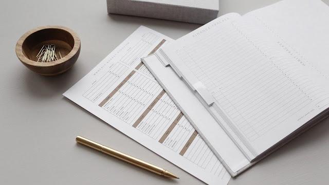 Mesa com cadernos, planilhas e caneta em cima