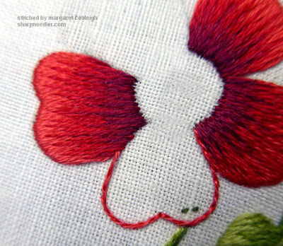 Split stitching the outline of a needlepainted rose petal.