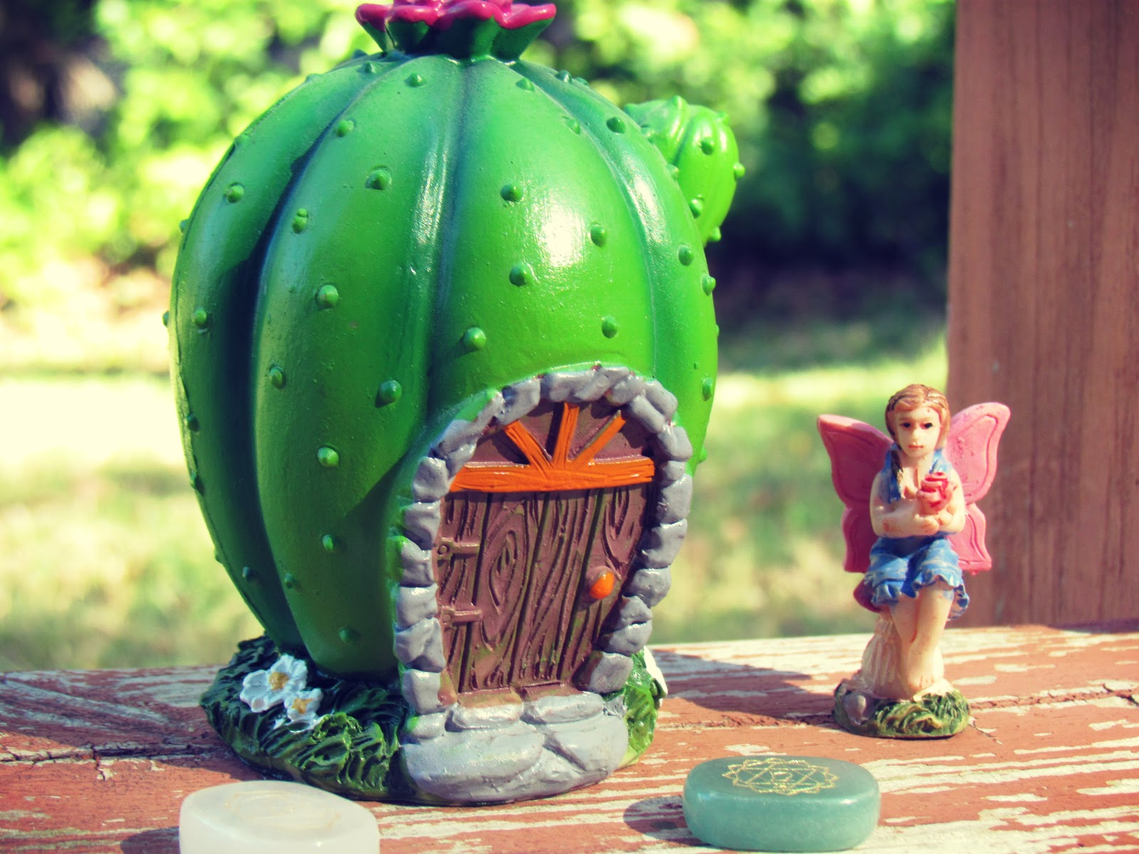 A cactus fairy house with a fairy figurine in the backyard in a landscape in Florida