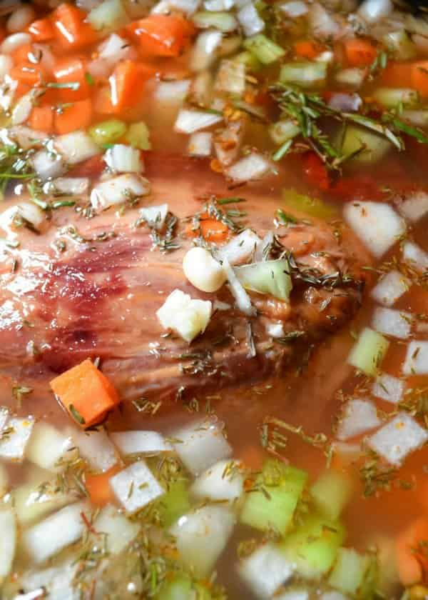 Crock Pot filled with ham hock, onion, celery, carrots, garlic, chipotle pepper, thyme, seasonings and water.
