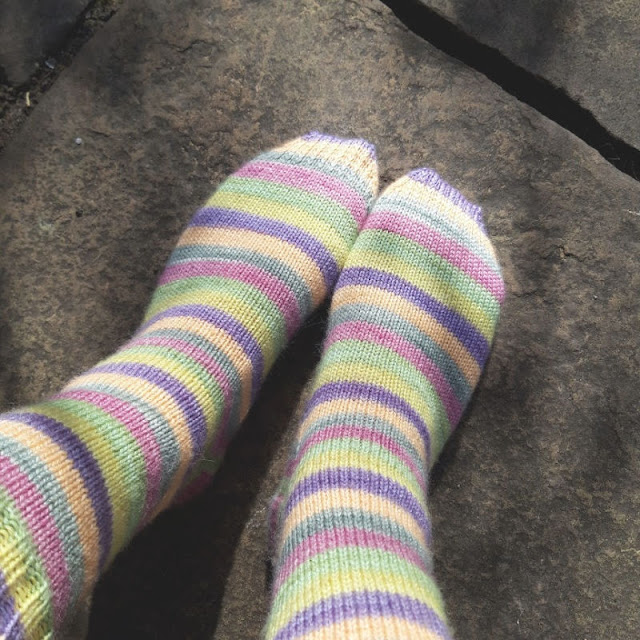 Image shows a vertical picture of the pair of feet in the striped socks