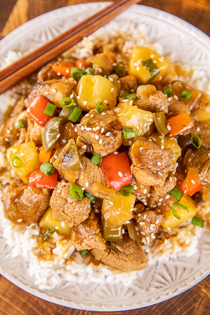 Sweet & Sour Pork on a plate with rice and chopsticks