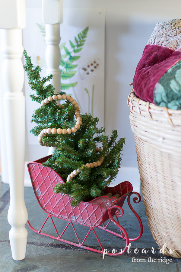 decorative red Santa sleigh with small tree and wood bead garland