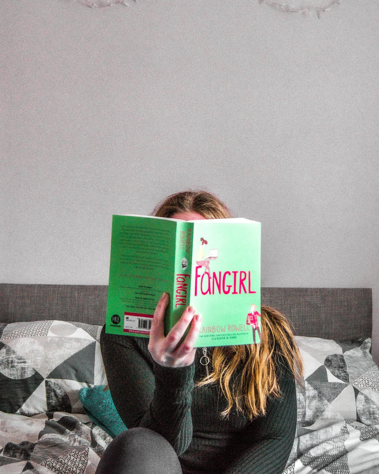 a female sat on a bed facing the camera, holding the book Fangirl in front of her face