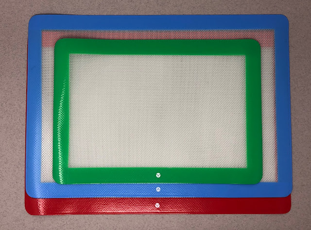 3 silcone baking mats with red, blue and green borders and see through white middle