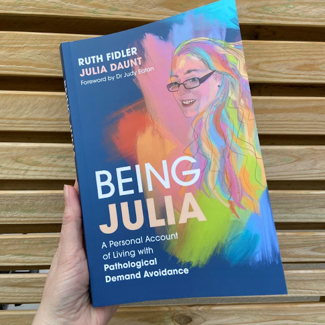 Blue front cover of Being Julia book with title text and text saying a personal account of living with pda. also has colourful line drawing of Julia