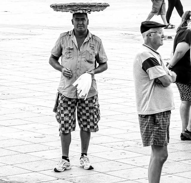 Una persona da la espalda a un vendedor ambulante. B&N