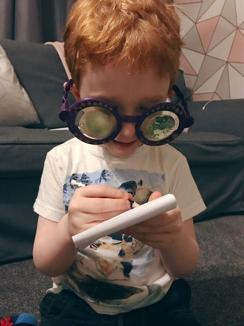 Little boy wearing the googly eye glasses and holding the pad and pen