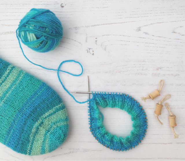 A ball of yarn in shades of blue and green, a partially-knitted sock on a circular needle and the toes of a finished sock on a background of white boards. To the right are some small cotton reel stitch markers