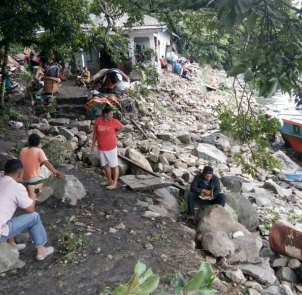 Warga menyaksikan kondisi rumah yang rusak akibat luapan Danau Toba.