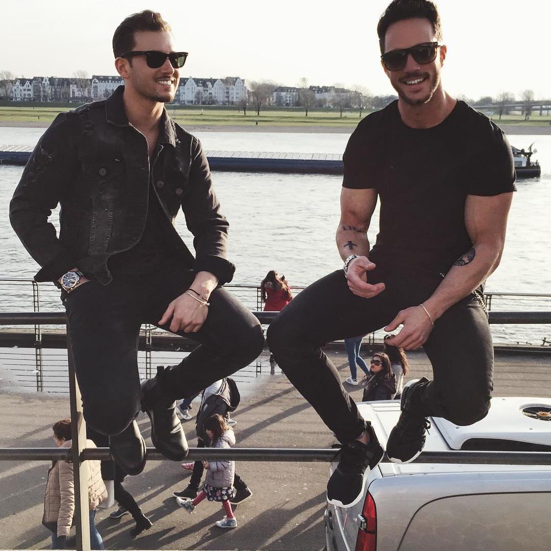 two-handsome-gentlemen-black-clothes-dark-sunglasses-smiling
