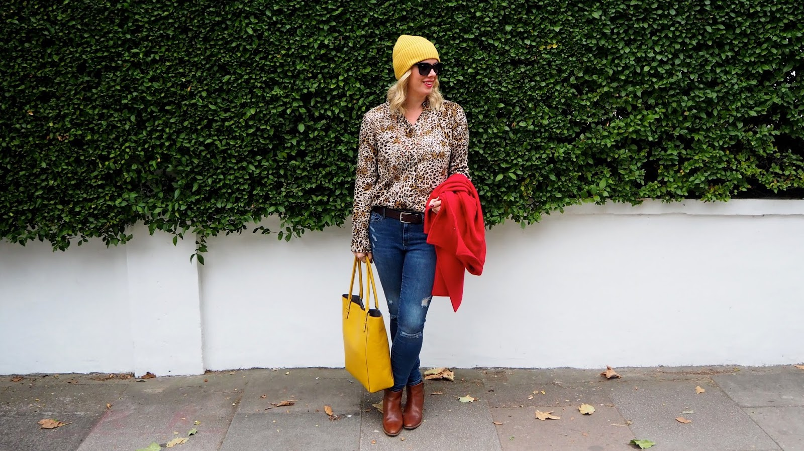 leopard print blouse, jeans, brown belt, brown boots, red coat, yellow hat & bag and black sunglasses