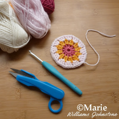 Yarns, thread snips, hook and crocheted motif