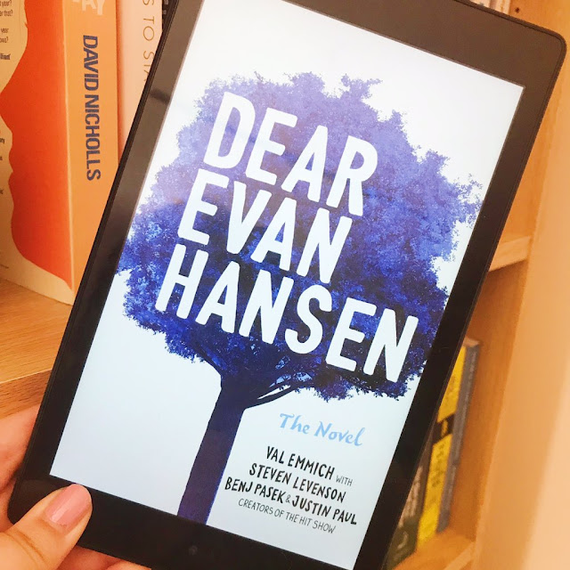 Dear Evan Hansen cover on my Kindle, held up in front of bookcase