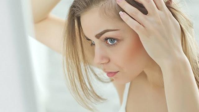 Mujer triste mirando como se le cae el pelo