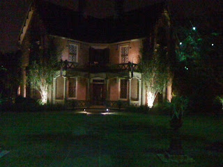 A view in front of a Saint Charles Avenue Mansion Lit Up at Night (exterior)