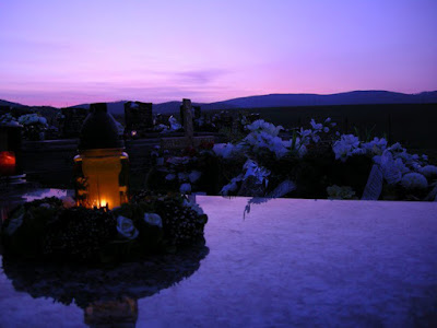 A blue and purple sunrise is visible at the top of the picture and reflected in the top of the tomb, upon which a candle is lit and glowing with a wreath around it and flowers on another grave..