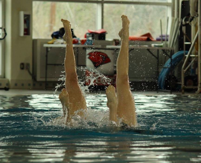 Synchronized swimmers' legs sticking out of a pool
