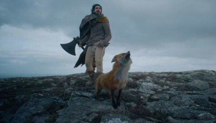 Imagem: o personagem Gawain, segurando o machado, em cima de uma charneca cheia de pedras, com o céu cinzento ao fundo, enquanto uma raposa uiva para cima, próxima dos seus pés;
