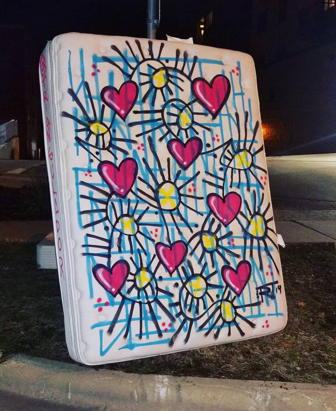 Image contains street art outdoors at night on mattress