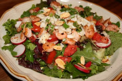 A mix of lettuces with vegetables, and a little crab and shrimp, tossed with a good olive oil and vinegar dressing makes this a light main dish salad.