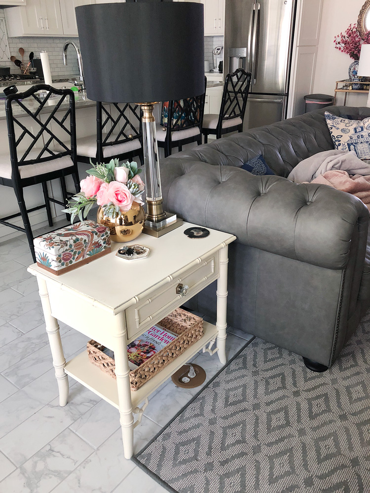 Chinoiserie inspired bamboo vintage end tables with a gray chesterfield sofa
