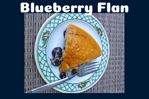 This is a baked custard and a piece of it Sliced Blueberry Flan on a fruit trim Lenox china plate showing the flan that will be served