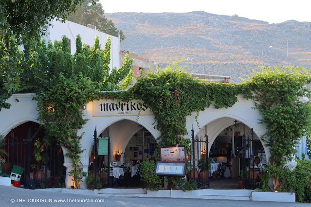 The by wine overgrown entrance of a vaulted whitewashed courtyard restaurant tiled with pebbles in front of a mountain range.