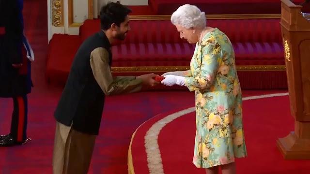 Ayman Sadiq taking award from Queen Elizabeth II