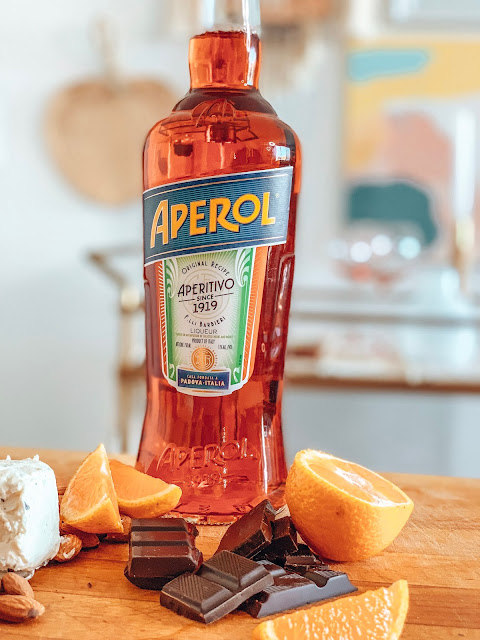 sliced oranges and a bottle of aperol on a cutting board