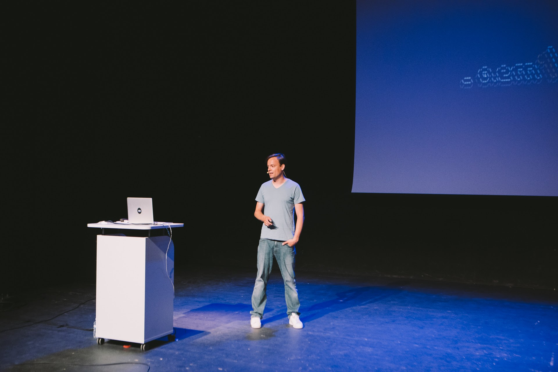 Image shows Martin Kleppe standing alone onstage. His computer is on a podium in front of him and a large screen is up on the wall behind him.