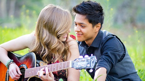 Romantic Young Couple Playing Guitar