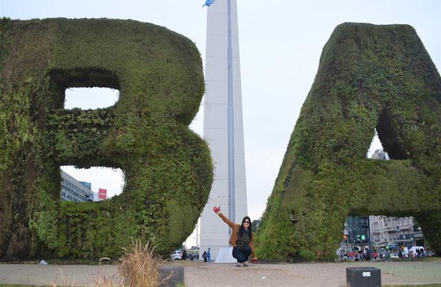 mulher com os braços abertos no meio as letras B e A