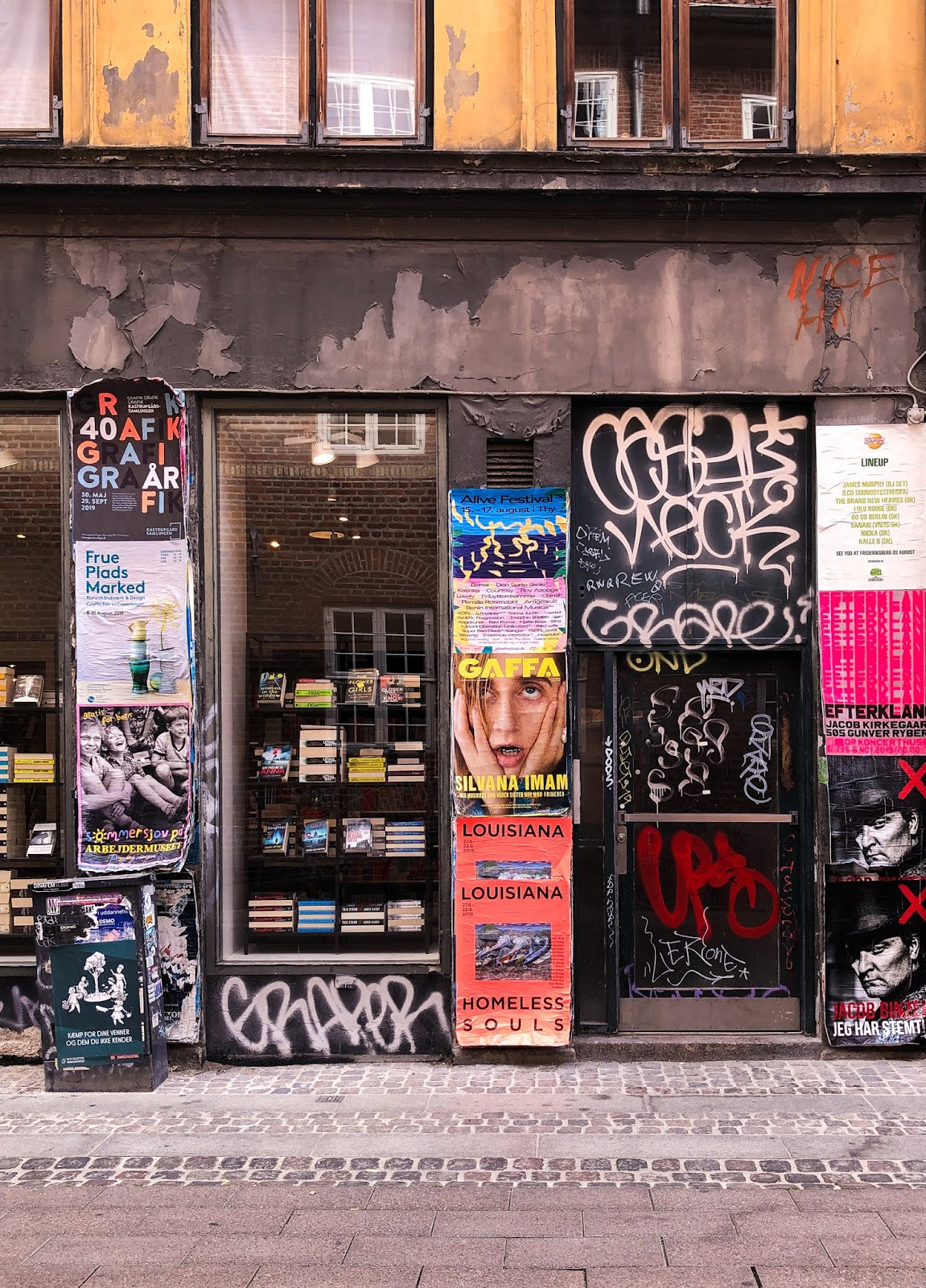run down shop front in Copenhagen featuring promotional posters and graffiti