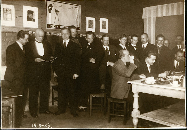 Mustavalkoinen kuva. Miehiä  juhlavissa mustissa puvuissaan huoneessa.  Taustalla valokuvia ja postereita. Osa seisoo, osa istuu.