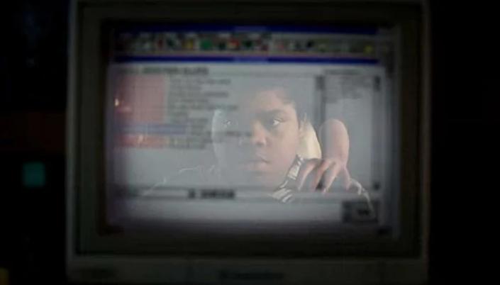 Imagem: o reflexo do personagem Josh, um menino negro na tela de um computador em que se vê um chat de fórum e uma mão no ombro dele.