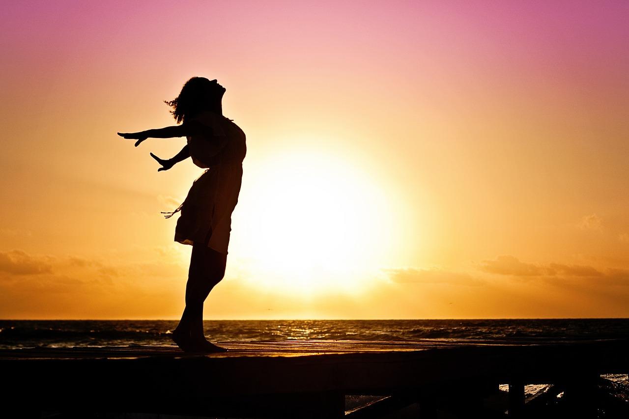 mulher de braços abertos em um por do sol