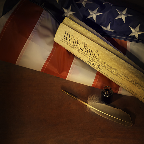 photograph of american flag, constitution and old quill