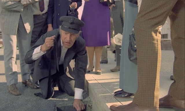 Bruce Forsyth dressed as a chauffeur kneeling over a drain