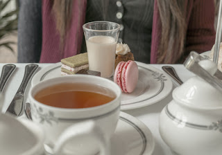 a cup of tea and dessert plate from an afternoon tea