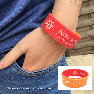 """Close up of person with their hand in their pocket, wearing a wide red wristband that says """"Now is tough, but it will improve"""""""